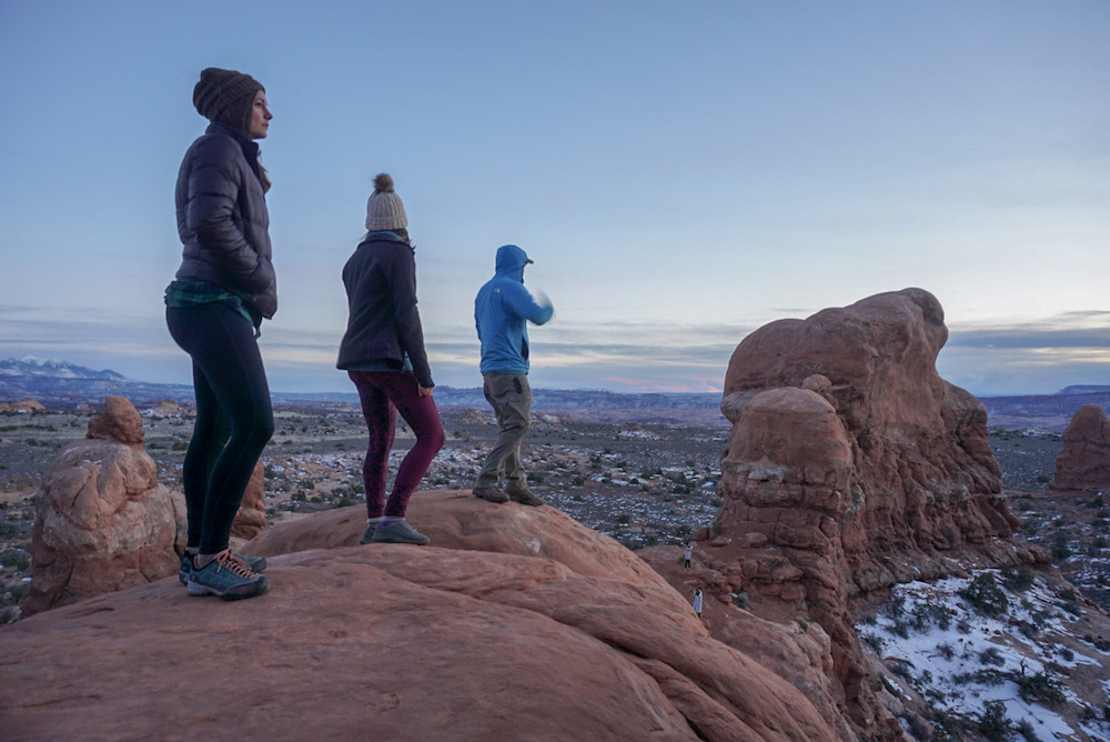 Three hikers admiring the view during their Arches National Park itinerary.